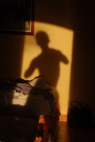 Karykaturalny cień człowieka na ścianie pokoju hotelowego