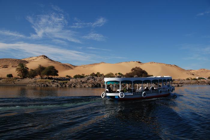 Statek na rzece płynącej przez Saharę. W tle wydmy i bezchmurne niebo.