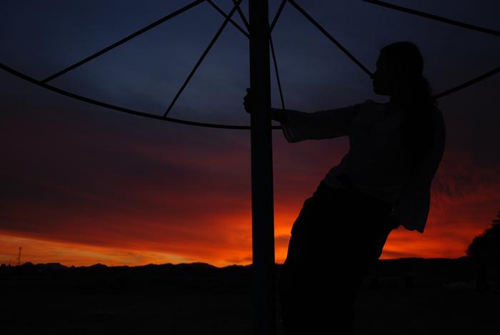 Kobieta w efektownej pozie na tle nieba oświetlonego zachodzącym słońcem