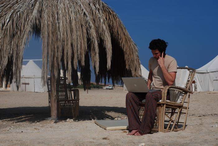 Mężczyzna na plaży siedzący na wiklinowym krześle trzyma na kolanach laptopa i rozmawia przez telefon. W tle namioty beduinów, obok parasol zbudowany z liści palmowych